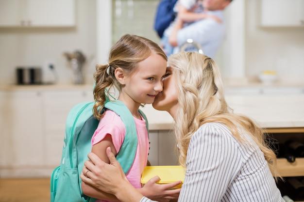 学校に行く間娘にキスする女性