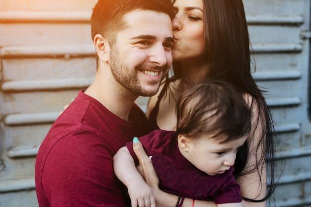 女性は頭の上に彼女の夫にキスをし、この1は赤ん坊を持っています