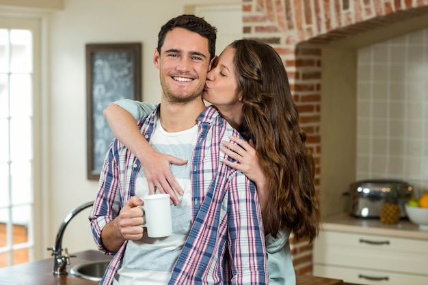 Woman kissing man from behind while having coffee in kitchen