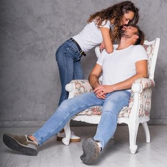 Woman kissing man in armchair