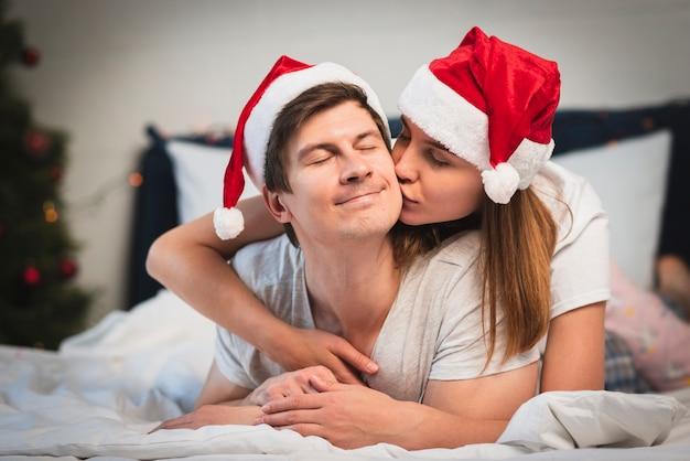 女性がベッドで男にキス