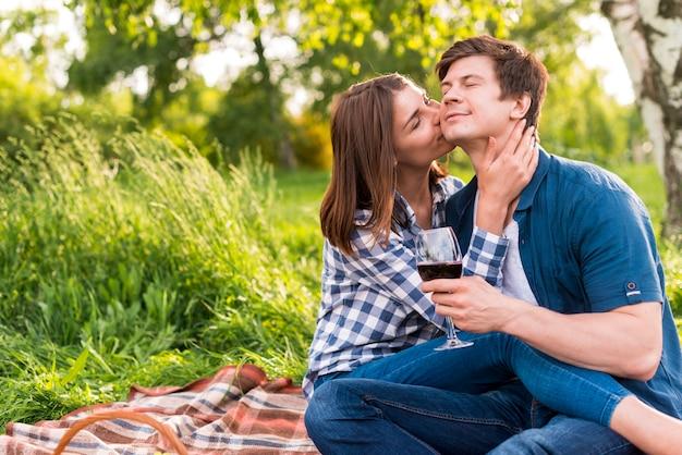 ピクニックをしながら頬に男にキスをする女性
