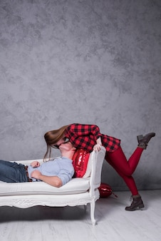Woman kissing man on sofa