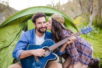 Woman kissing man with guitar
