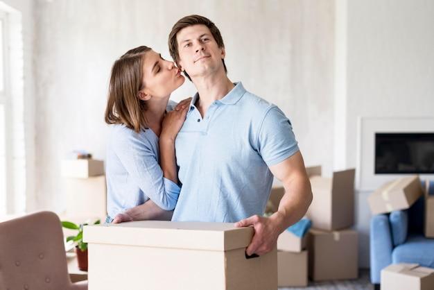 Женщина целует партнера дома в день переезда