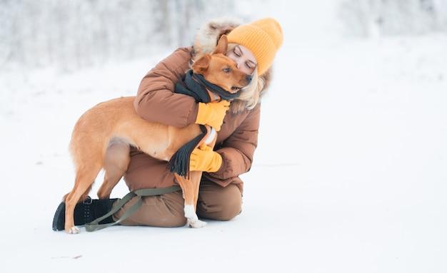 冬の森で赤い雑種犬にキスする女性。
