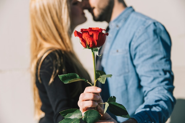 Woman kissing with boyfriend and showing rose