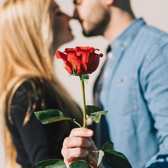 Woman kissing with man and showing rose
