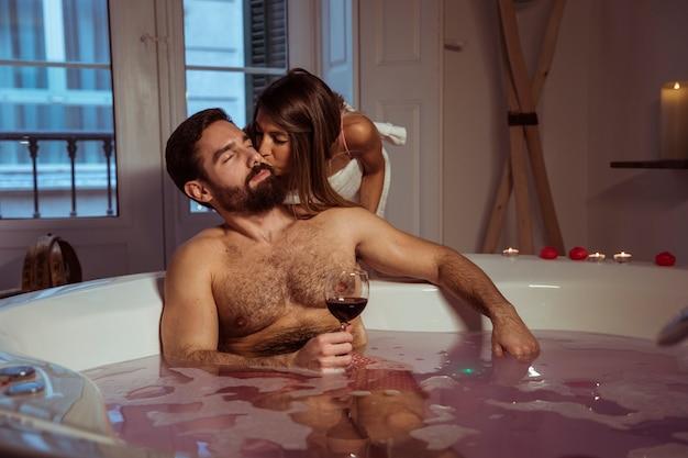 스파 욕조에서 음료의 유리를 가진 젊은이 키스하는 여자