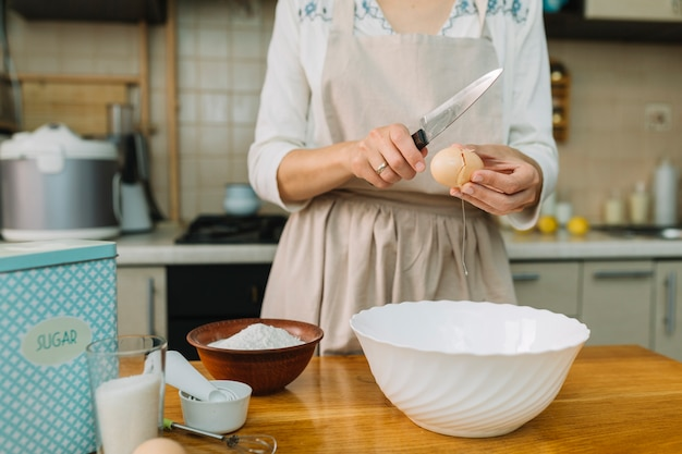 Woman in kitchen breaking egg for preparing bowl