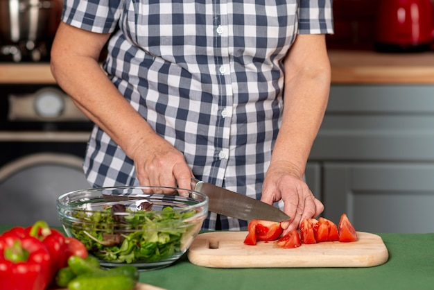 Woman in kitchen cooking salad