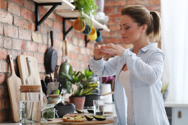Woman in the kitchen eating a sandwich