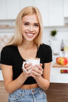 Donna in cucina e tenendo la tazza di caffè