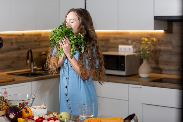 Woman in kitchen holding green fresh aromatic parsley leaves. young housewife in jeans dress cooking. healthy eating, vegetarian food, dieting and people concept. for weight loss and detox. vertical