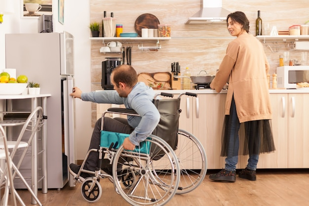 Woman in kitchen looking at husband with walking disability trying to open refrigerator door. disabled paralyzed handicapped man with walking disability integrating after an accident.