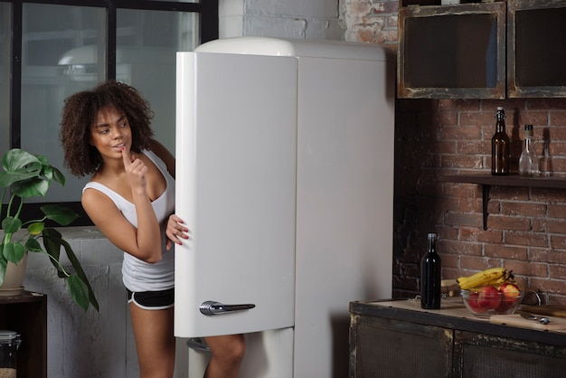 Woman in kitchen looking into fridge