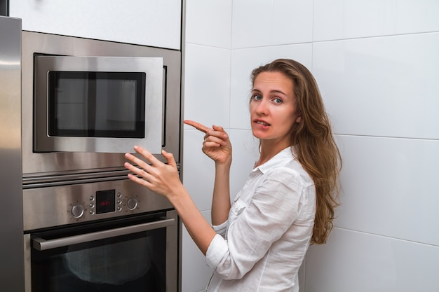 Woman in the kitchen opened the microwave oven door and is surprised by the food she has cooked.