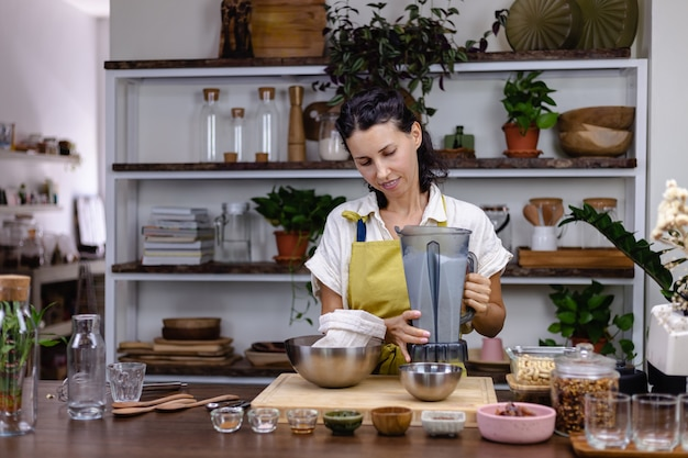 Woman in kitchen with chia pudding making process