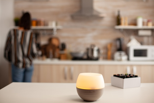 Woman in the kitchen with essential oils diffuser