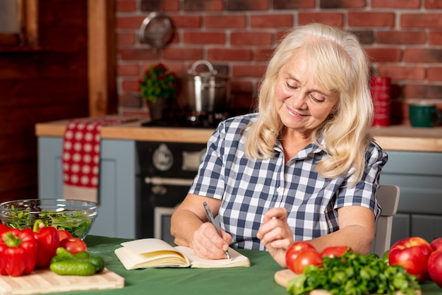Woman in kitchen writing recipe