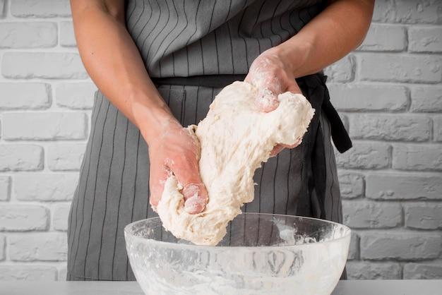 Woman kneading dough over bowl