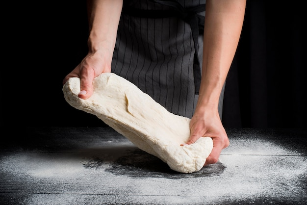 Woman kneading dough on table