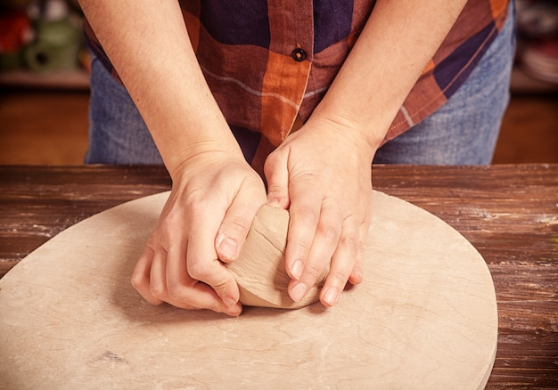 Woman kneads the clay