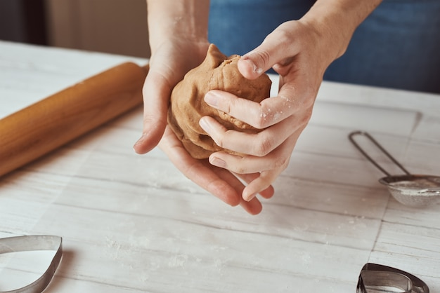 Woman kneads dough with hands in kitchen