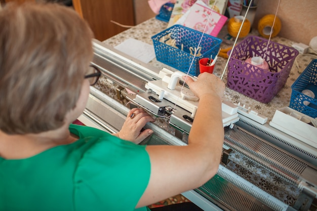A woman knits on a knitting machine, working with her hands