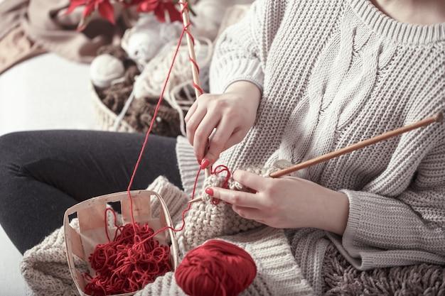女性はソファの上の編み針を編む