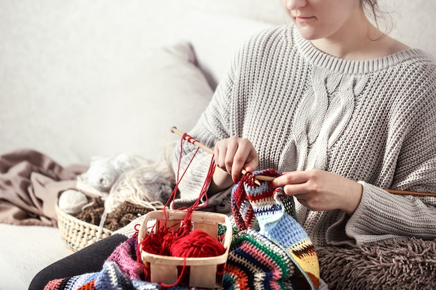 女性はソファの上で編み針を編む
