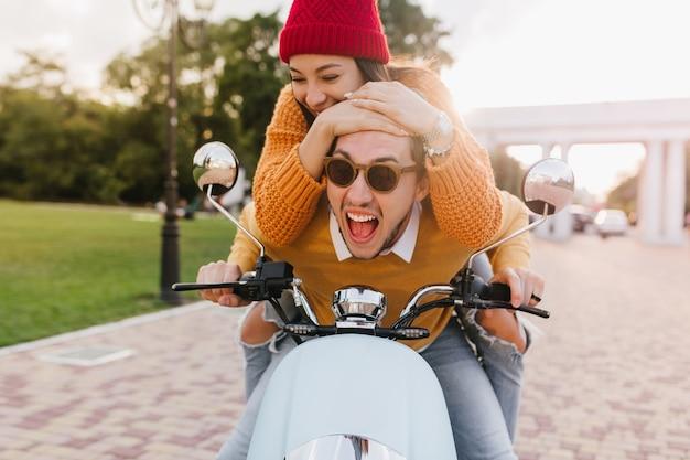 Donna con cappello rosso lavorato a maglia che tiene la testa del marito mentre guida uno scooter