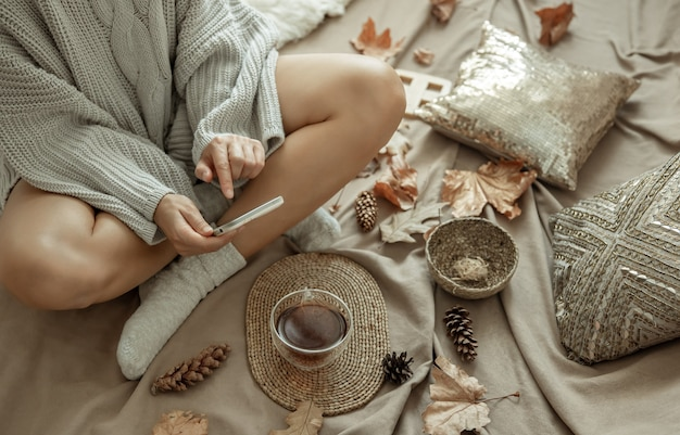 A woman in a knitted sweater takes a picture of a cup of tea in bed among cones and leaves, autumn composition, content.