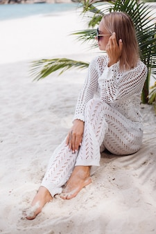 Woman in knitted white clothes on beach