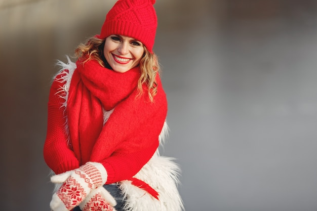 Donna in sciarpa e cappello invernale lavorato a maglia che guarda l'obbiettivo con un sorriso