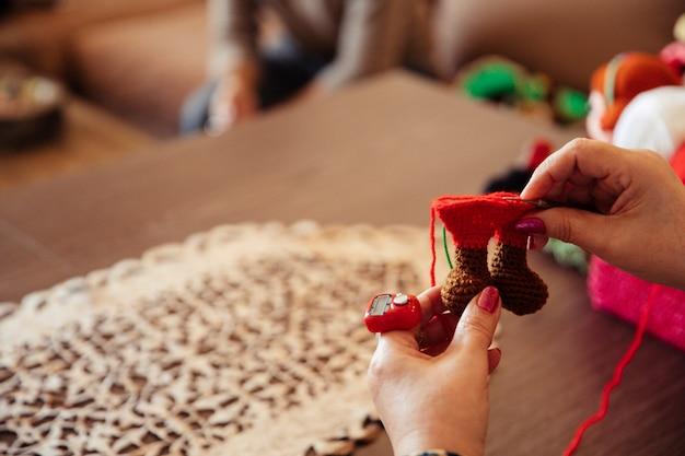 赤い糸で飾りを編み物をする女