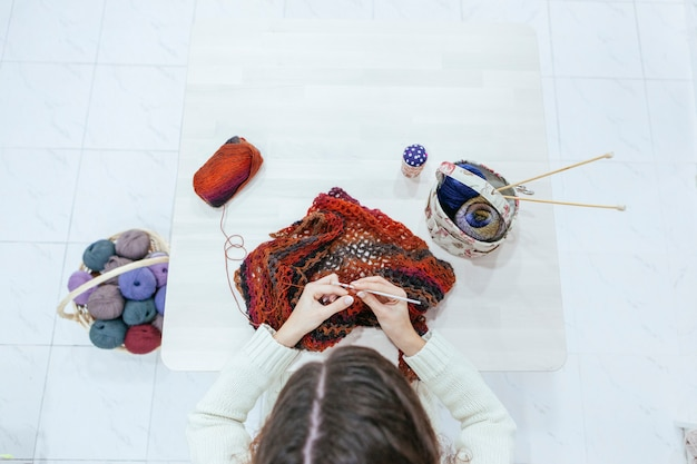 Woman knitting a woolen scarf on a white table