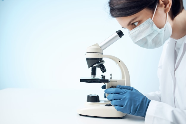 Woman laboratory assistant medical mask microscope diagnostics biotechnology