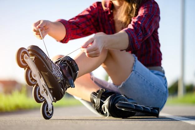 女性はインラインスケートのローラースケートをひもで締めます。屋外のティーンエイジャーのローラーブレード。