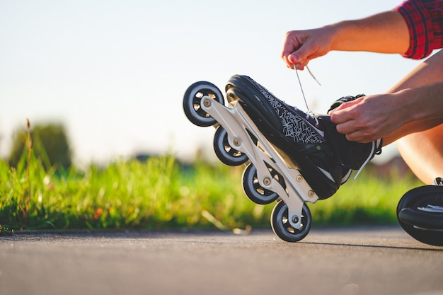 Woman laces roller skating for inline skating. teenager rollerblading outdoors.