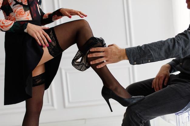 女性のレースのセクシーなストッキングは彼女の下着を脱ぐ男の手は黒人女性のパンティーを脱ぐクローズアップ