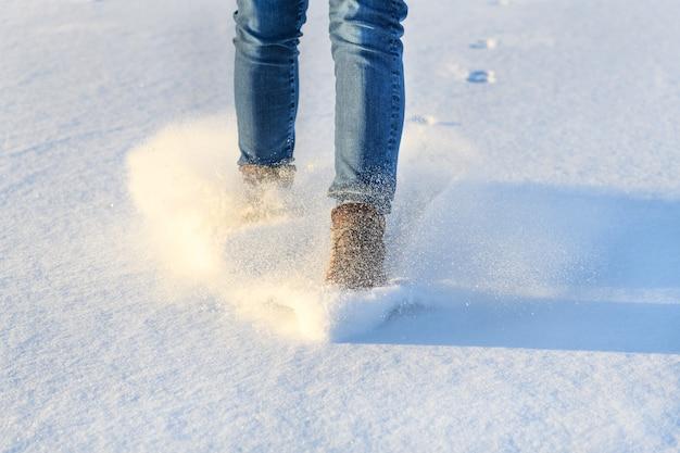Женщина лагом в ботинке скользит по льду, покрытому снегом. зимняя прогулка в концепции теплой и удобной обуви.