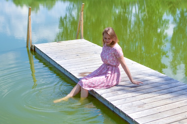 Woman on lake on the pier sits resting in summer. quiet rest on a pond by the nature