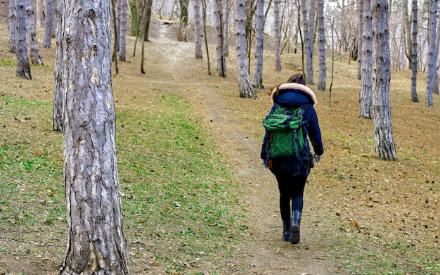 Woman in a late winter forest with backpack
