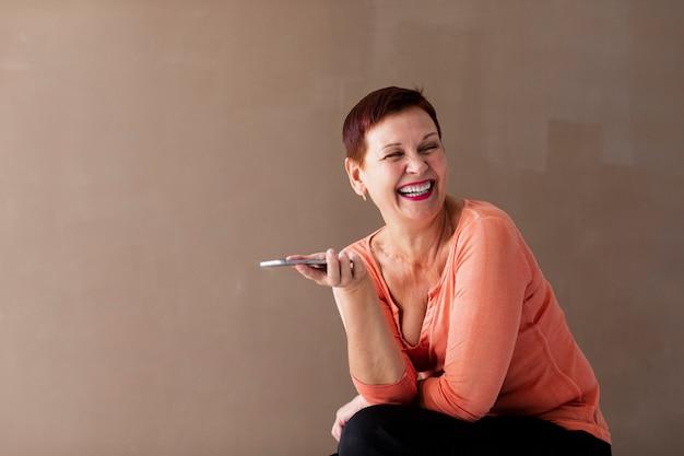 Женщина смеется и держит телефон