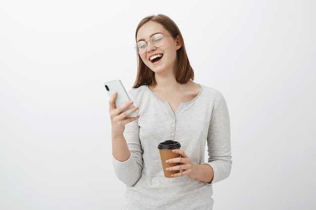 Женщина громко смеется, читая смешную шутку или мем в интернете, глядя на экран смартфона, держа в руках бумажный стаканчик с кофе, весело проводя время в ожидании друга в кафе