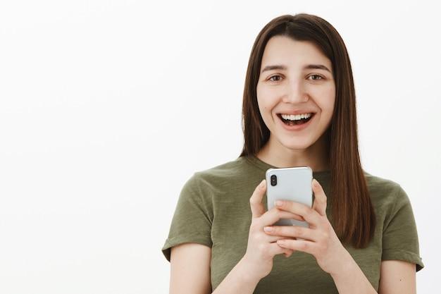 スマートフォンを手に持ったスマートフォンで撮った面白い写真を笑っている女性