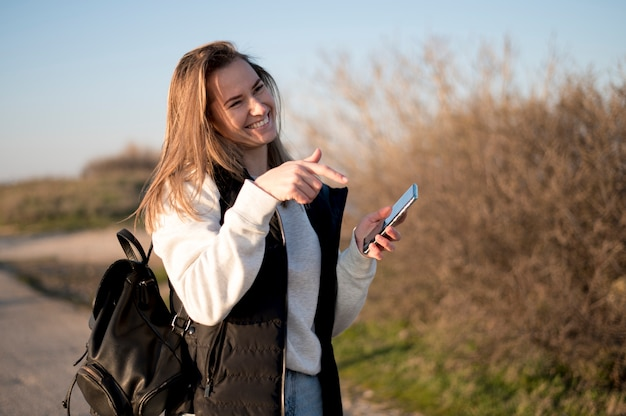 Woman laughing and pointing at her phone