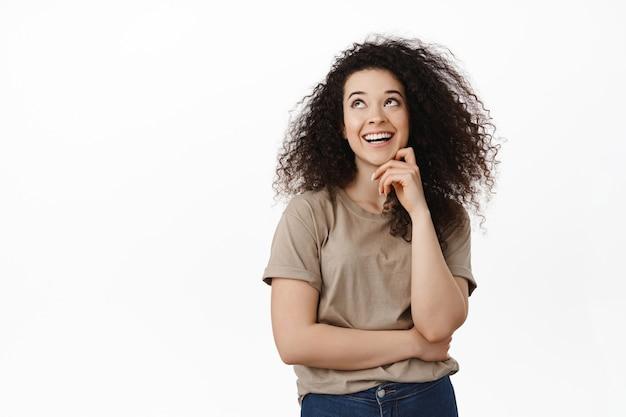 笑って、白い歯で笑って、左上隅で幸せそうに見える女性、白のtシャツに立っています。