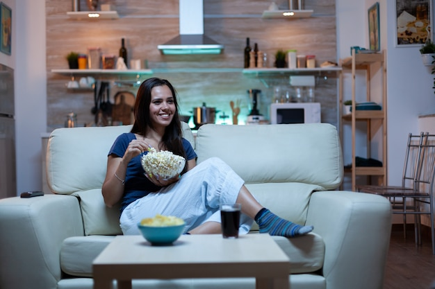 Woman laughing watching tv and eats snacks. young happy, excited, amused, home alone lady enjoying the evening sitting on comfortable couch dressed in pajamas eating popcorn in front of television